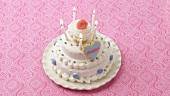 Fünf brennende Kerzen auf einer weissen Torte