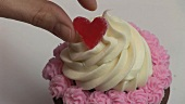 Decorating cupcake with jelly heart
