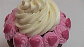 Chocolate cupcake with cream, pink buttercream & sugar hearts