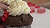 Schokoladen-Cupcake mit roter Zuckercreme verzieren