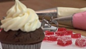 Chocolate cupcake with cream topping, red jelly hearts behind