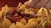 Dipping nachos in tomato salsa