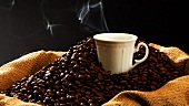 Sack of coffee beans and steaming cup of coffee