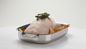Stuffed duck (oven-ready) with oranges in a roasting dish