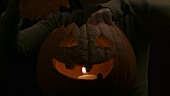 Lighting a tealight in a Halloween pumpkin