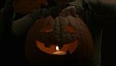 Teelicht in einem Halloweenkürbis anzünden
