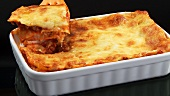 Taking a portion of lasagne out of a baking dish