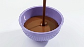 Pouring melted couverture chocolate into a dish