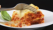 Cutting a bite-sized piece of lasagne with a fork