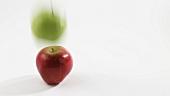 Grüner Apfel fällt auf roten Apfel