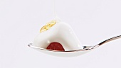 Raspberry, cream and honey on spoon
