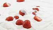 Strawberries falling into cream