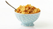 A bowl of cornflakes with a spoon