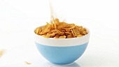 Putting cornflakes into a bowl