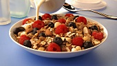 Pouring milk over muesli with berries