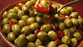 Taking a spoonful of marinated green olives