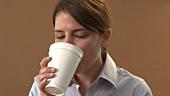 Junge Frau trinkt Kaffee aus einem Papierbecher