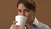 Young woman drinking coffee out of a paper cup