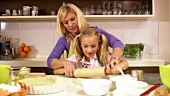 Mother and daughter rolling out pastry together