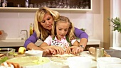 Mother and daughter making cinnamon buns together