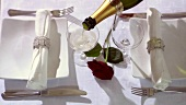 Elegantly laid table with red rose and champagne