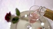 Ein Glas Rosesekt einschenken