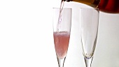 Pouring two glasses of rosé sparkling wine