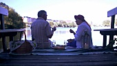 Mature couple picnicking on landing stage