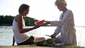 Two women cutting up watermelon at picnic