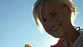 Junge Frau isst Wassermelone beim Picknick