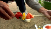 Preparing tomato, pepper and leek skewers for barbecuing