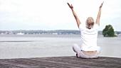 Frau sitzt auf einem Steg und macht Körperübungen