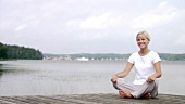 Blond woman sitting cross-legged on a landing stage