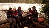 Freunde sitzen am Feuerstelle und essen