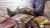 Man grilling freshly caught fish