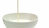 Pouring milk into a bowl (close-up)