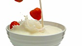 Putting milk and strawberries into a bowl (close-up)