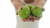 Junge Frau hält drei grüne Äpfel