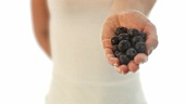 Young woman holding fresh blueberries