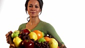 Woman holding basket of fresh fruit