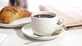 Eine Tasse Kaffee mit Croissant