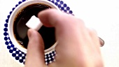 Putting several sugar cubes into a cup of coffee