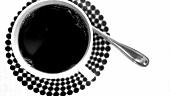 Mehrere Würfelzucker in eine Tasse Kaffee geben