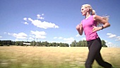 Blond woman jogging beside cornfield