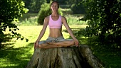 Woman in lotus position on a tree stump in a park