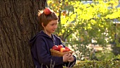 Apple falling from the head of a boy leaning against a tree