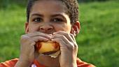 Junge isst Cheeseburger