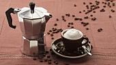 Cappuccino mit Milchschaum, Espressokanne und Kaffeebohnen