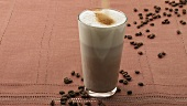 Sprinkling caffe latte with brown sugar and stirring it