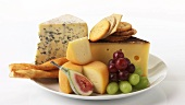 Various cheeses with savoury biscuits and grapes
